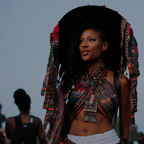 afropunk fan in a colorful outfit and large hat