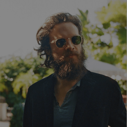 Father John Misty in front of trees