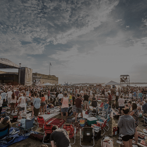 People seated in lawn chairs enjoying a beautiful sunny day at newport folk festival